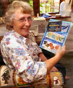 Mary Mayne holding a copy of her book
